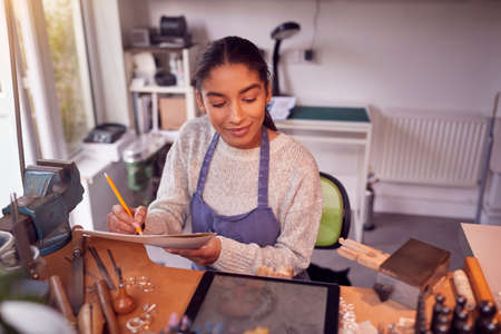 Female Jeweller Looking At Ring Design On Digital Tablet In Studio