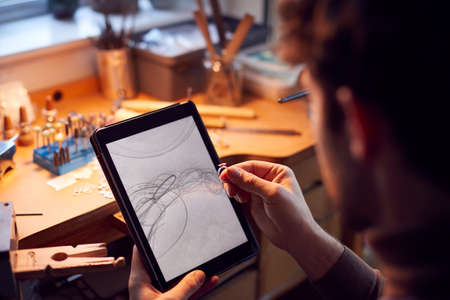 Close Up Of Male Jeweller Looking At Ring Design On Digital Tablet In Studio