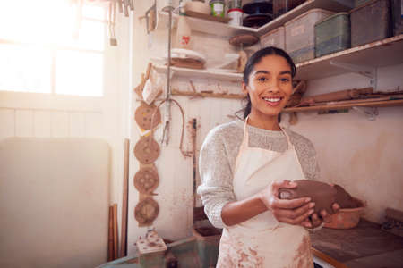 Portrait Of Female Potter Wearing Apron Holding Lump Of Clay In Ceramics Studio