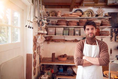 Portrait Of Male Potter Wearing Apron In Ceramics Studio
