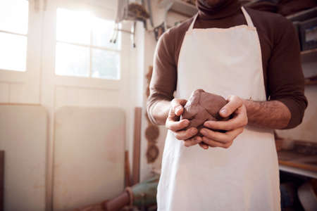 Close Up Of Male Potter Wearing Apron Holding Lump Of Clay In Ceramics Studio