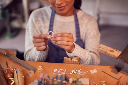 Close Up Of Female Jeweller At Bench Checking Ring She Is Working On In Studio Archivio Fotografico
