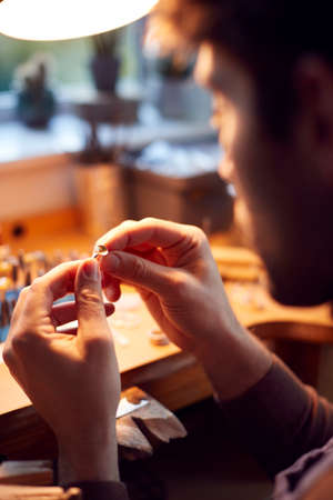 Close Up Of Male Jeweller Looking At Setting For Ring In Studio