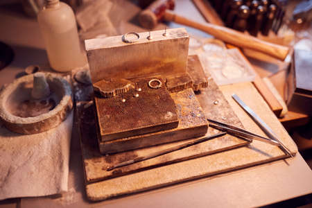 Close Up Of Jewellers Workbench With Tools And Designs  In Studio
