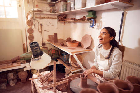 Female Potter Shaping Clay For Pot On Pottery Wheel In Ceramics Studio