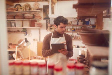 Male Potter In Ceramics Studio Checking Orders Using Digital Tablet