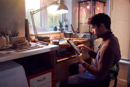 Male Jeweller Looking At Ring Design On Digital Tablet In Studio Archivio Fotografico