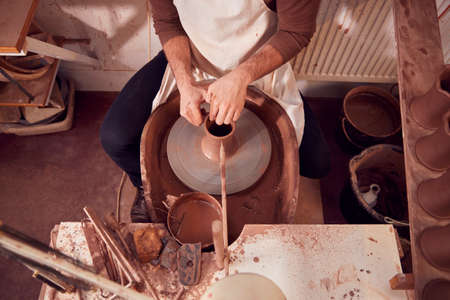Close Up Of Male Potter Shaping Clay For Pot On Pottery Wheel In Ceramics Studio