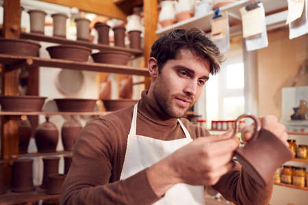 Male Potter Fitting Clay Handles To Mugs In Ceramics Studio
