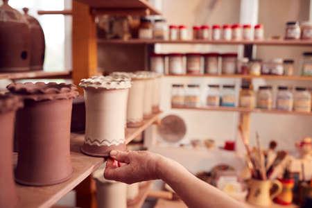 Close Up Of Potter Putting Glazed Clay Vase On Shelf In Ceramics Studio Archivio Fotografico