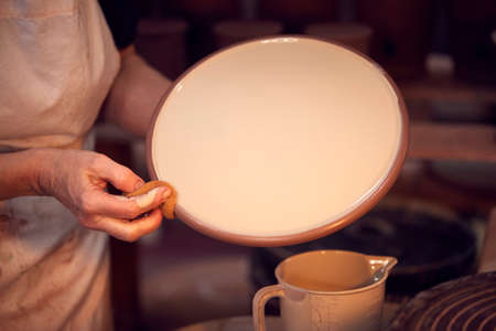 Close Up Of Potter Applying Glaze To Clay Plate In Ceramics Studio