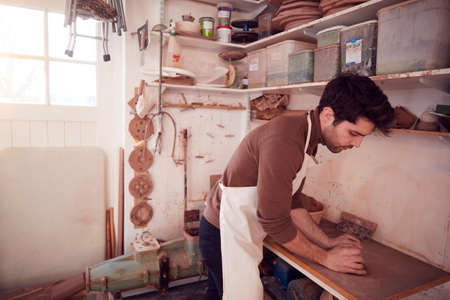 Male Potter Wearing Apron Rolling Out Lump Of Clay In Ceramics Studio