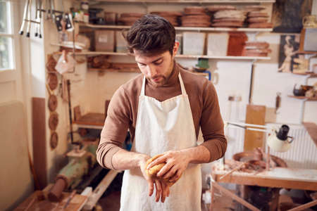 Male Potter Cleaning Hands With Sponge In Ceramics Studio