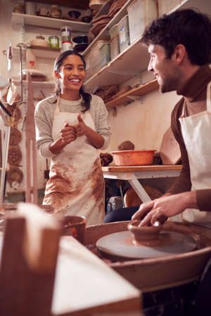 Couple Running Bespoke Pottery Business Working In Ceramics Studio Together Archivio Fotografico