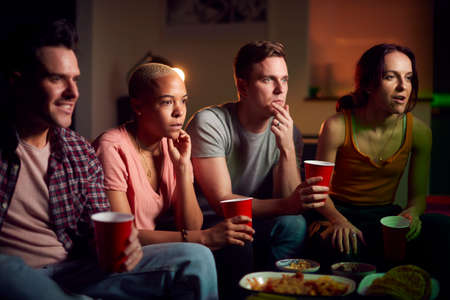 Group Of Friends With Drinks Sitting On Sofa At Home Watching Horror Movie Together 免版税图像