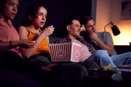 Group Of Friends Eating Popcorn Sitting On Sofa At Home Watching Horror Movie Together 免版税图像