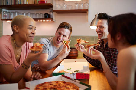 Group Of Gay Friends Meeting At Home And Eating Takeaway Pizza