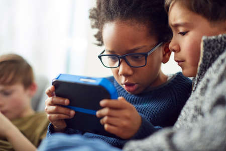 Group Of Young Boys Gaming Together On Hand Held Devices At Home