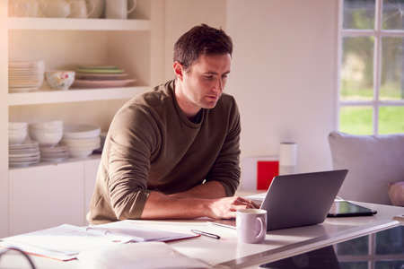 Man With Laptop Working From Home On Kitchen Counter