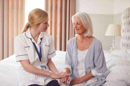 Female Doctor Making Home Visit To Senior Woman For Medical Check Offering Reassurance