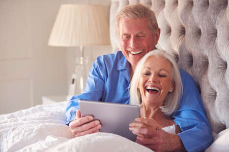 Senior Couple At Home In Bed Self Isolating Using Digital Tablet During Covid 19 Lockdown Фото со стока