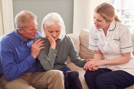 Female Doctor Giving Bad News To Senior Couple During Home Health Visit