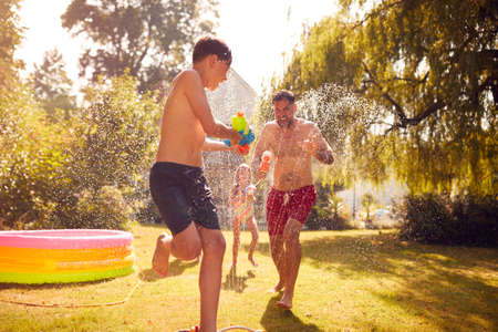Family Wearing Swimming Costumes Having Water Fight With Water Pistols In Summer Garden