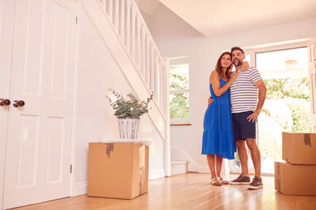 Mature Couple With Boxes Standing By Front Door Of New Home On Moving Day