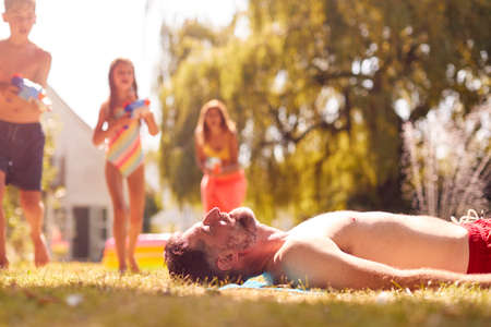 Family Squirting Father With Water Pistols In Summer Garden As He Sunbathes 免版税图像