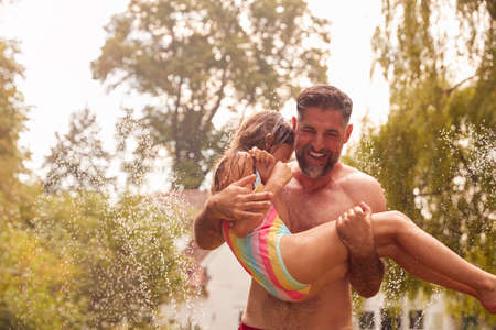 Father Carries Daughter Through Water From Garden Sprinkler Having Fun Wearing Swimming Costumes
