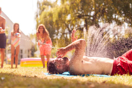 Family Squirting Father With Water Pistols In Summer Garden As He Sunbathes