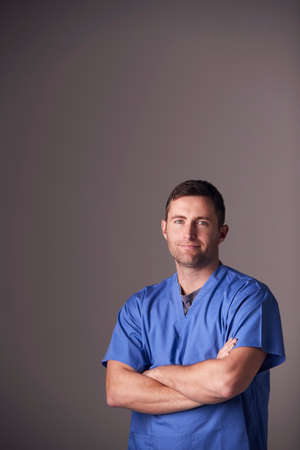 Studio Portrait Of Male Nurse Wearing Scrubs Standing Against Grey Background