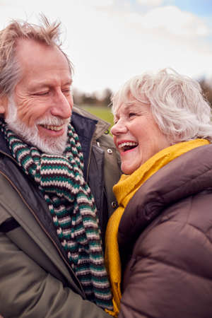 Close Up Of Loving Senior Couple Enjoying Autumn Or Winter Walk Through Park Together
