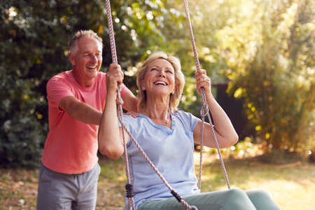 Retired Couple Having Fun With Man Pushing Woman On Garden Swing