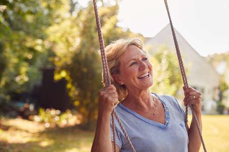 Carefree Smiling Retired Woman Having Fun On Garden Swing Standard-Bild