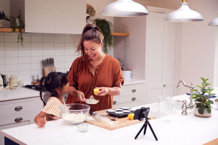Asian Mother And Daughter Baking Cupcakes In Kitchen At Home Whilst On Vlogging On Mobile Phone