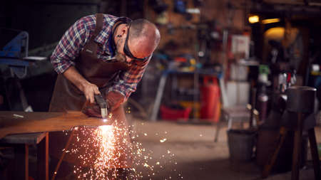 Male Blacksmith Using Plasma Cutter To Cut Shape From Sheet Metal In Forge Banque d'images