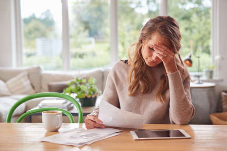 Worried Woman With Digital Tablet Sitting At Table At Home Reviewing Domestic Finances