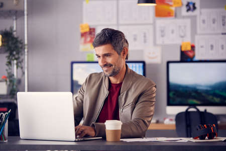 Mature Male Advertising Marketing Or Design Creative In Studio Sitting At Desk Working On Laptop Stockfoto
