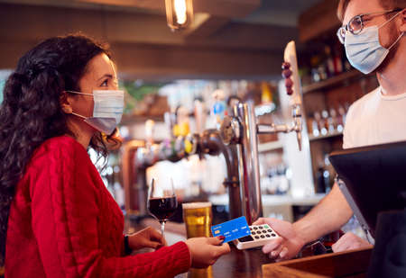 Female Customer Wearing Mask In Bar Making Contactless Payment For Drinks During Health Pandemic Stock Photo