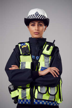 Studio Portrait Of Serious Young Female Police Officer Against Plain Background