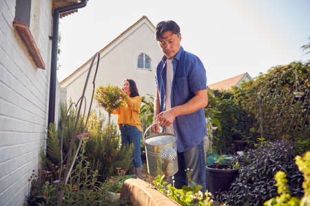 Mature Asian Couple At Work Watering And Caring For Plants In Garden At Home Standard-Bild