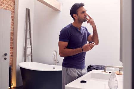 Man Wearing Pyjamas At Home In Modern Bathroom Putting On Moisturizer Looking In Mirror
