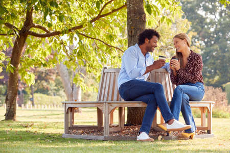 Loving Mature Couple Relaxing Sitting Together On Bench Under Tree In Summer Park With Coffee