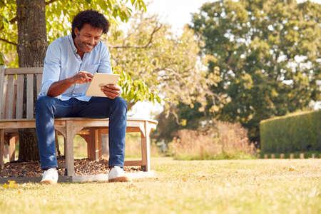 Mature Man Sitting On Bench Under Tree In Summer Park Using Digital Tablet