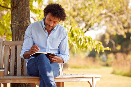 Mature Man Sitting On Park Bench Under Tree Writing In Notebook