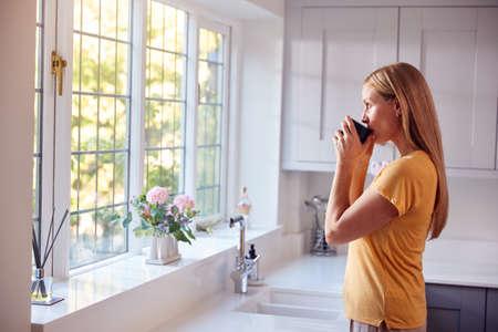 Mature Woman At Home With Hot Drink Standing By Kitchen Window