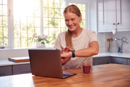 Mature Woman Wearing Fitness Clothing At Home Logging Activity From Smart Watch Onto Laptop