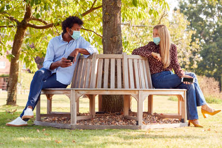 Socially Distanced Couple Wearing Masks Meeting In Outdoor Park During Health Pandemic