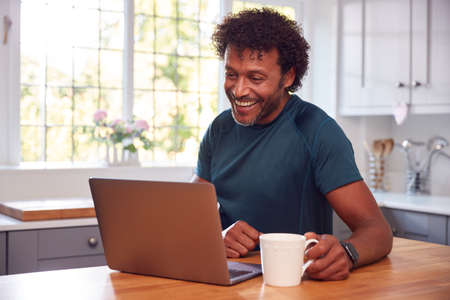 Mature Man In Kitchen Working From Home On Laptop Computer